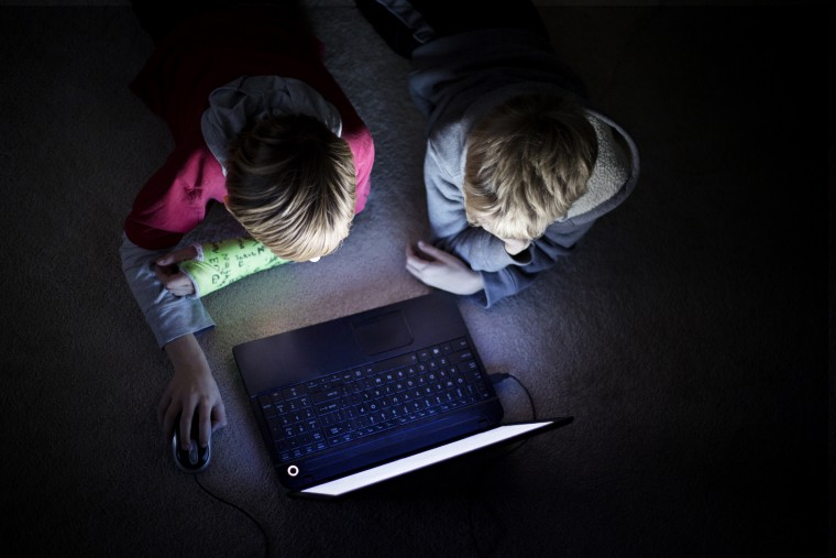 Image: Two boys using laptop in dark room