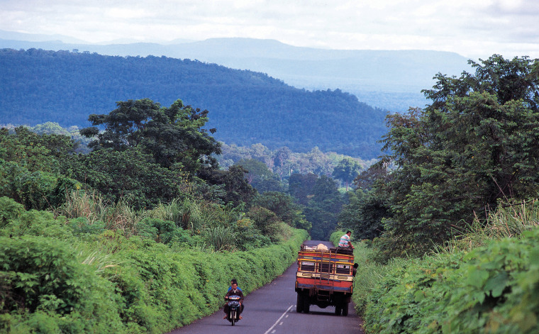 A local bus on a road in the lush Boloven Plateau in southern Laos.