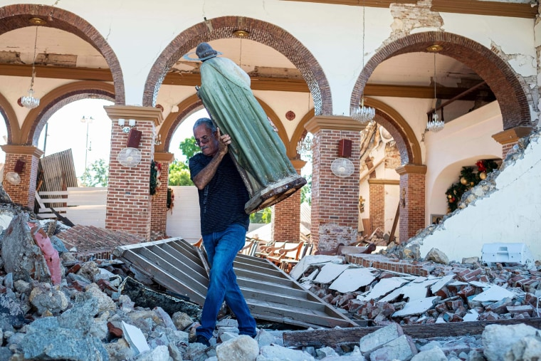 A man carries a St. Jude statue from the Inmaculada Concepcion church that collapsed after an  earthquake hit the island in Guayanilla, Puerto Rico on Jan.  7, 2020.
