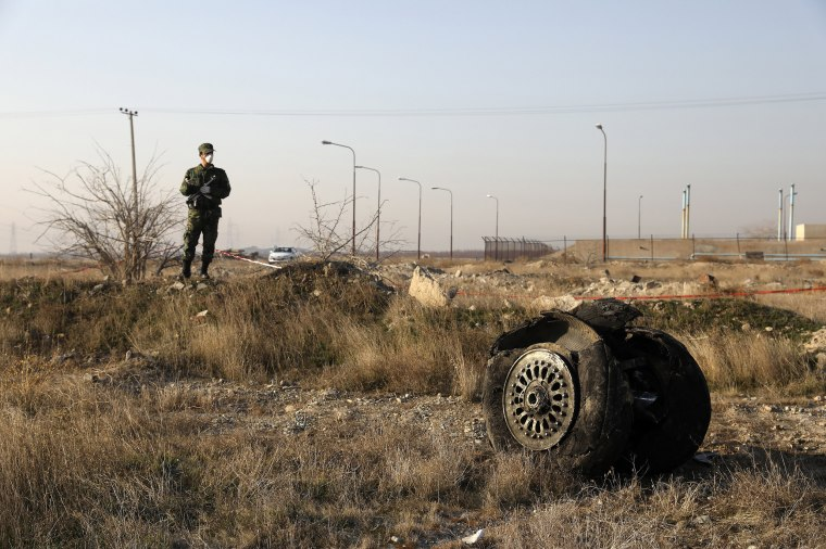 A police officer stands guard next to debris from an Ukrainian plane that crashed in Shahedshahr, southwest of the capital Tehran, Iran, on Jan. 8, 2020. A Ukrainian airplane carrying 176 people crashed on Wednesday shortly after takeoff from Tehran's main airport, killing all onboard.