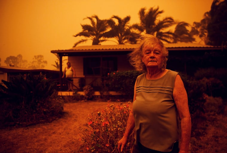 Nancy Allen stands outside a house as high winds push smoke and ash from the Currowan Fire towards Nowra, New South Wales, Australia on Jan. 4, 2020.