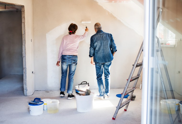 Rear View Of Senior Couple Painting Walls In New Home, Relocation Concept