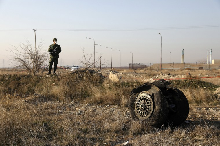 Image: A police officer stands guard as debris is seen from an Ukrainian plane which crashed in Shahedshahr, southwest of the capital Tehran