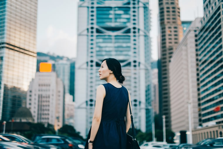 Image: Successful young businesswoman looking away with confidence standing against urban cityscape
