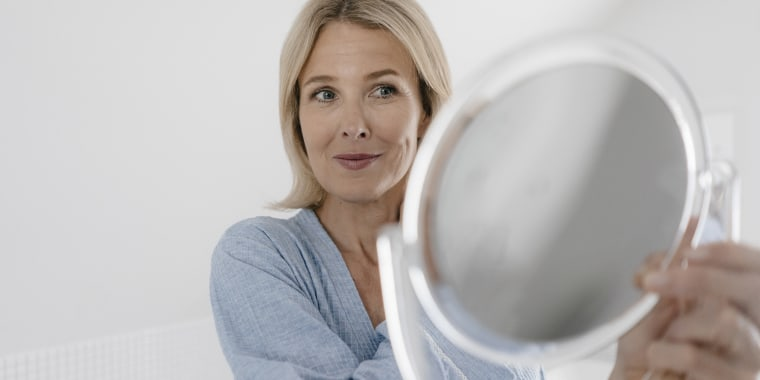 Mature woman looking in beauty mirror in bathroom