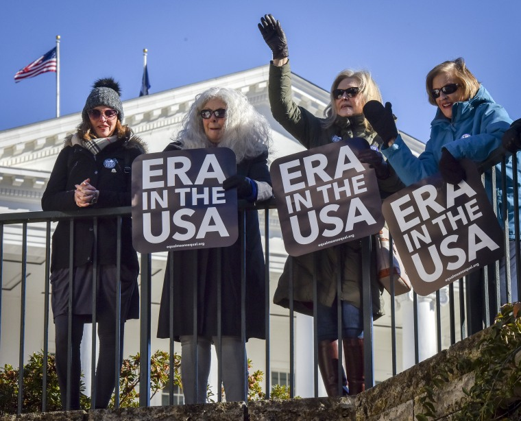 Supporters of the ERA amendment wave at the start of the Virginia General Assembly, in Richmond, Va., on Jan. 8, 2020.
