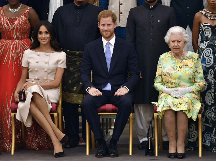 Image: Britain's Queen Elizabeth, Prince Harry and Meghan, Duchess of Sussex pose for a group photo at the Queen's Young Leaders Awards Ceremony at Buckingham Palace in London
