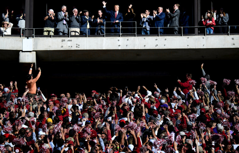 Image: President Donald Trump and first lady Melania Trump wave to fans at football game between Louisiana State University and Alabama in Tuscaloosa, Ala., on Nov. 9, 2019.