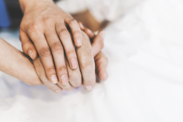 Cropped image of nurse holding man's hand