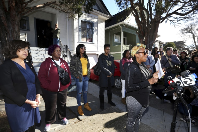 Dominique Walker, right, speaks for herself and on behalf of fellow Moms 4 Housing members during a press conference outside the house they have occupied in Oakland, Calif., on Jan. 10, 2020.