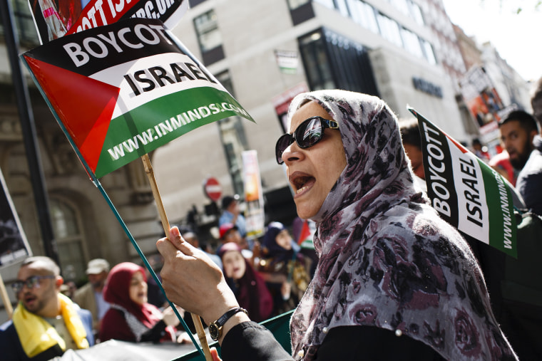A woman holds a 'Boycott Israel' flag during the annual pro-