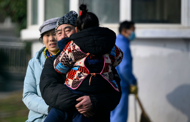 Image: A man holding her daughter leaves the Wuhan Medical Treatment Centre, where a man who died from a respiratory illness was confined, in the city of Wuhan, Hubei province