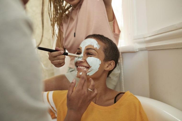 Image: Woman enjoying female friends applying cream on face