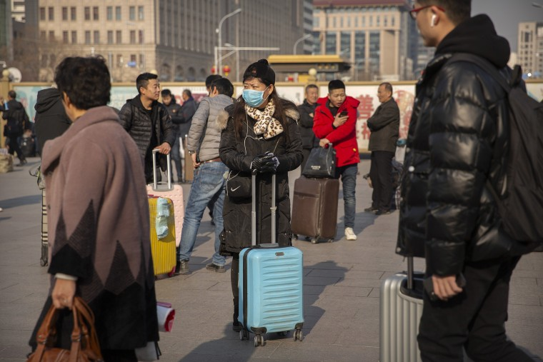 Image: A traveler wears a facemask as she stands near the Beijing Railway Station in Beijing,