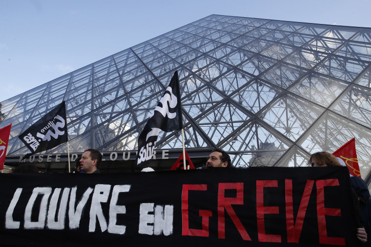 "Image: Striking employees hold a banner reading ""Louvre on strike"" outside the Louvre museum Friday, Jan. 17, 2020 in Paris."