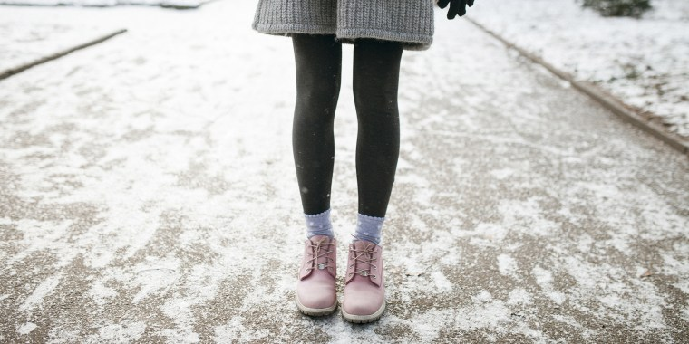 Legs of Caucasian woman standing in snow