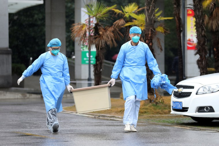 Image: Medical staff carry a box as they walk at the Jinyintan hospital, where the patients with pneumonia caused by the new strain of coronavirus are being treated, in Wuhan
