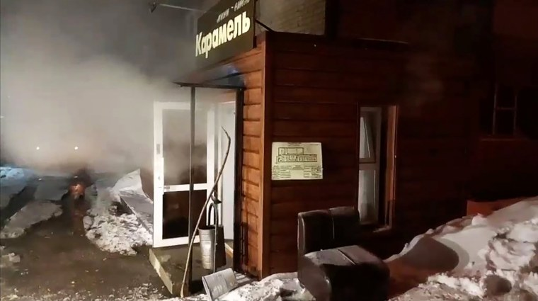 Image: Steam comes out from a door of the Mini Hotel Caramel after a hot water pipe exploded in the night and flooded a basement hotel room with boiling water, in Perm