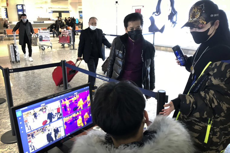 Image: Travelers pass through a health screening checkpoint at Wuhan Tianhe International Airport in Wuhan in southern China's Hubei province