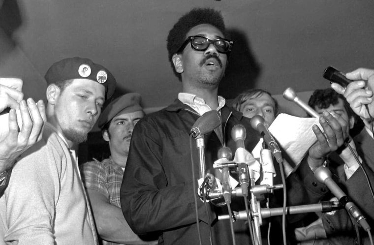 Bobby Rush, of the Illinois Black Panther party, reads a statement on June 4, 1969, following an early morning raid on the Chicago Panther headquarters by FBI agents. At left is Cha Cha Jimenez, of the Young Lords, a Puerto Rican group.