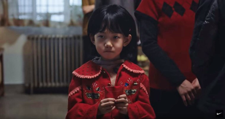 A young girl holds a red envelope given to her by her aunt in Nike's Lunar New Year ad.