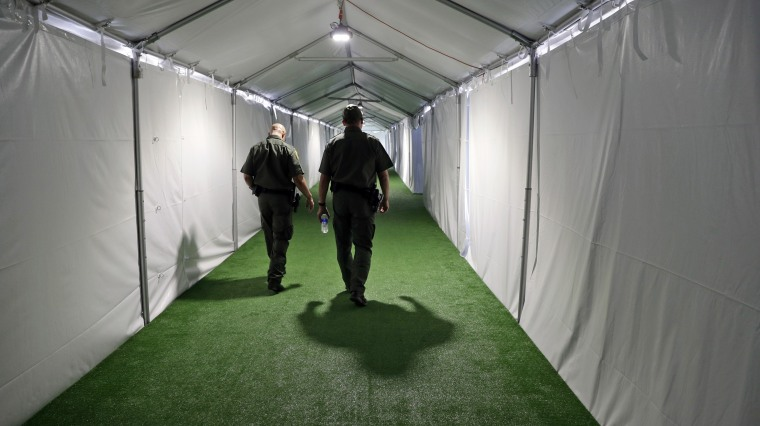 U.S. Border Patrol agents walk down the hallway of a U.S. Customs and Border Protection temporary facility near the Donna International Bridge in Donna, Texas, on May 2, 2019.