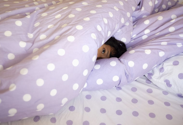 A little girl hides under the covers