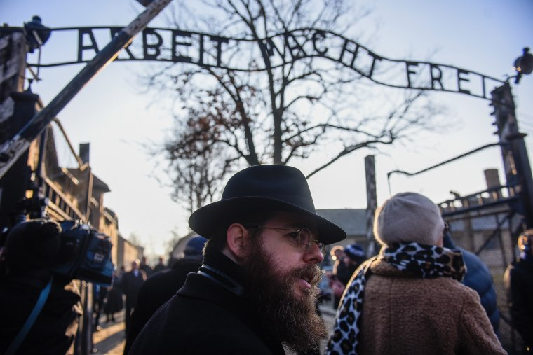 Image: Rabbi Shlomo Koves walks by the main gate of the former Auschwitz concentration camp bearing the motto Arbeit Macht Frei (Work brings freedom) on Jan. 21, 2020 in Oswiecim, Poland.