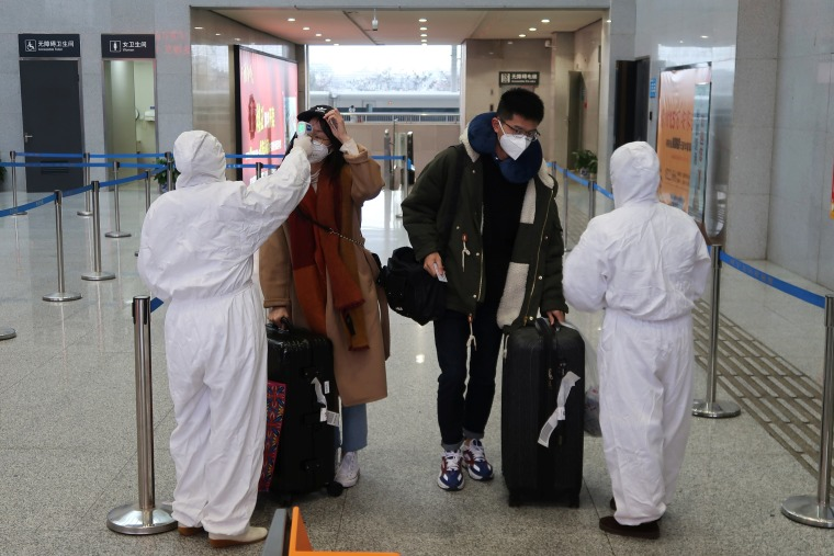 Image: Workers in protective suits check the temperature of passengers arriving at the Xianning North Station in Xianning, a city bordering Wuhan, on Friday.