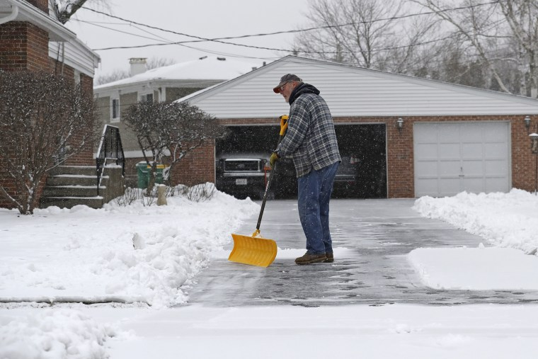 A man shovels the driveway of his house in Wheeling, Ill., on Jan. 23, 2020.