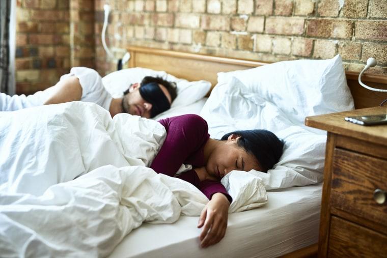 Woman asleep with hand on mattress and man wearing eye mask