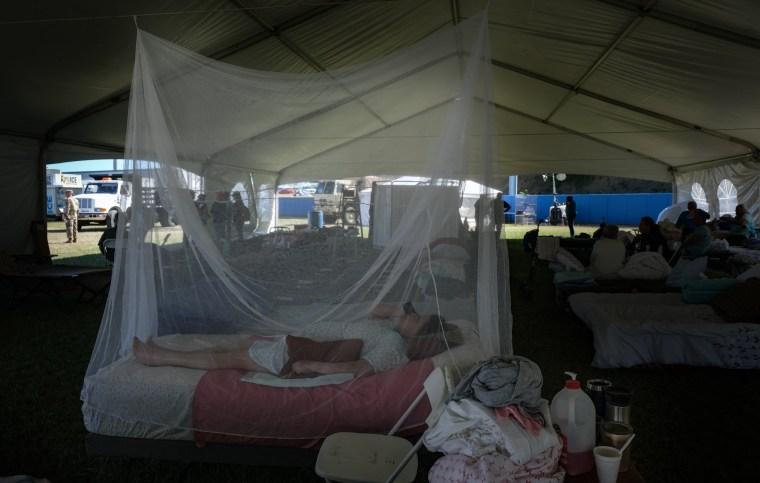 Image: A bedridden women lies under a mosquito net at Yauco Stadium