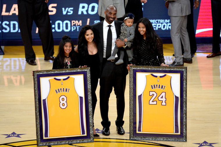 Image: Kobe Bryant poses with his family as both his Los Angeles Lakers numbers, 8 and 24, are retired at the Staples Center on Dec. 18, 2017.