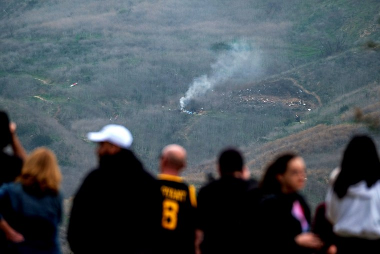 Image: People watch as smoke rises from the scene of a helicopter crash that killed basketball star Kobe Bryant in Calabasas, Calif., on Jan. 26, 2020.