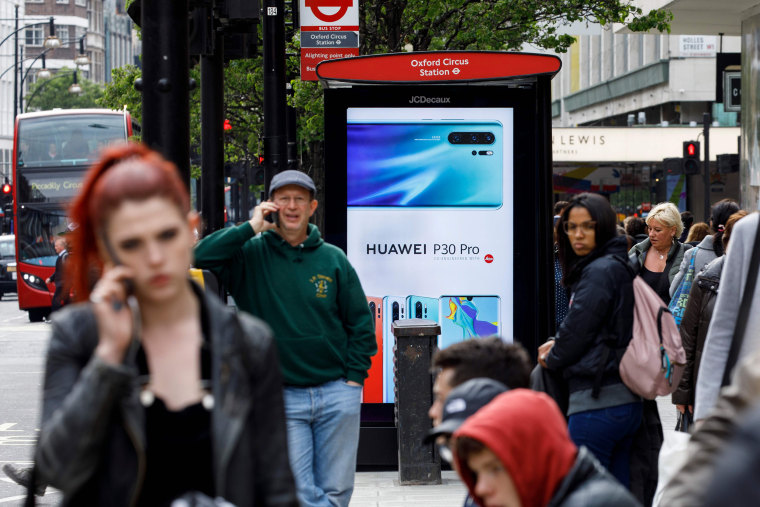 Image: Pedestrians use their mobile phones near a Huawei advert at a bus stop in central London