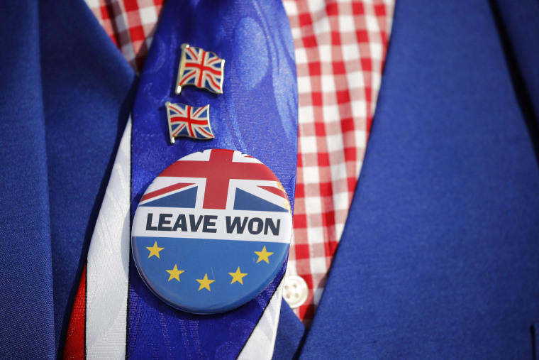 Image: Pro-Brexit activist Joseph Afrane wears a Leave button as he demonstrates outside the Houses of Parliament in Westminster, London