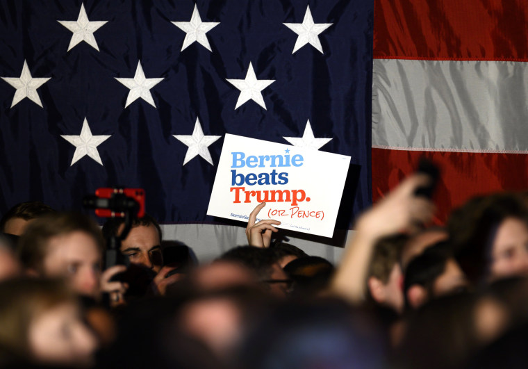 Image: Supporters wave signs for Sen. Bernie Sanders, I-VT, at a campaign event in Des Moines, Iowa, on Dec. 31, 2019.