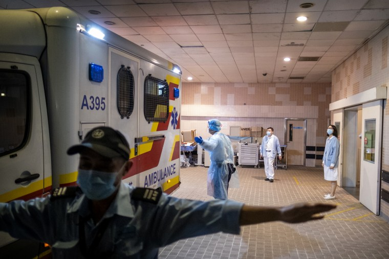 iMAGE: A security official stands guard as an ambulance arrives with a coronavirus patient at Princess Margaret Hospital in Hong Kong on Jan. 22, 2020.