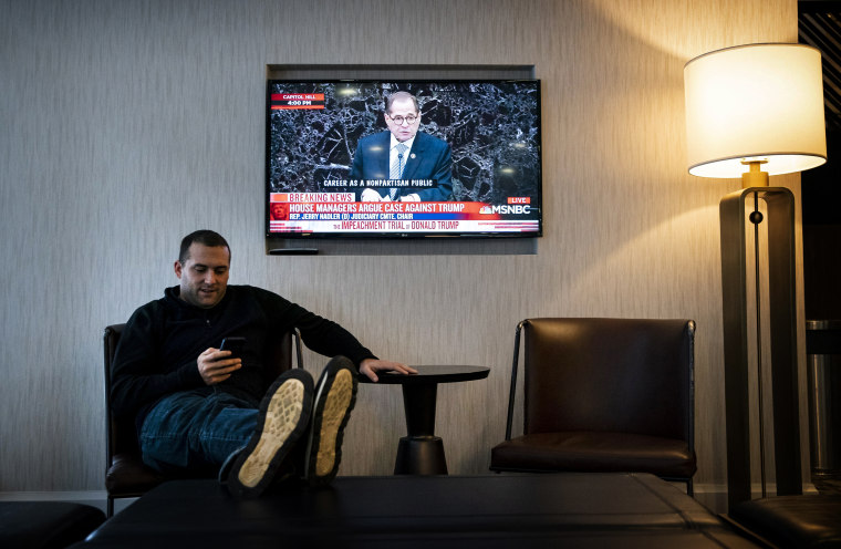 Image: A television plays impeachment coverage while a man looks at his cell phone in Des Moines, Iowa, on Jan. 22, 2020.
