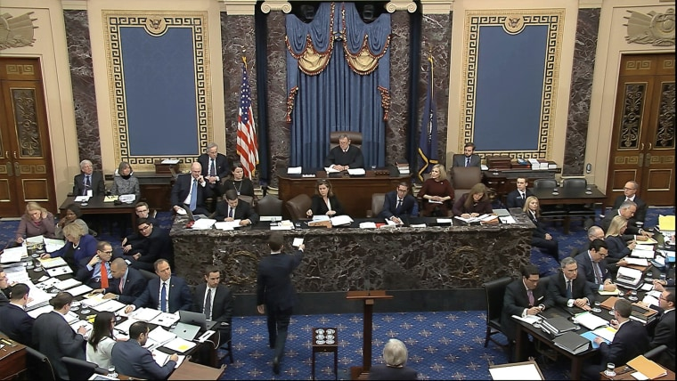 Image: A Senate page brings the first question to presiding officer Chief Justice of the United States John Roberts from the majority to read during the impeachment trial against President Donald Trump in the Senate at the U.S. Capitol