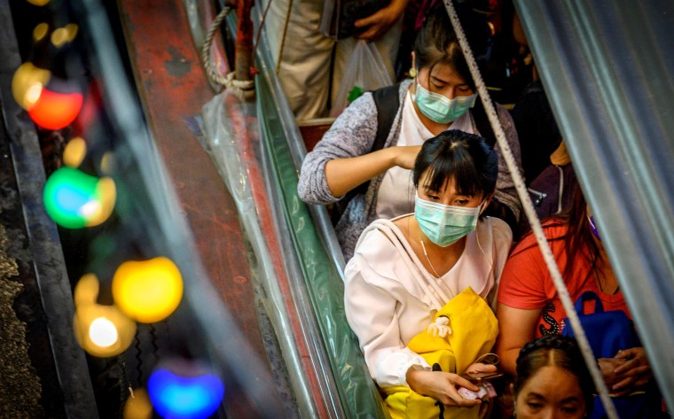 Image: Commuters wear masks to protect against the coronavirus at Pratunam Pier in Bangkok on Jan. 30, 2020.