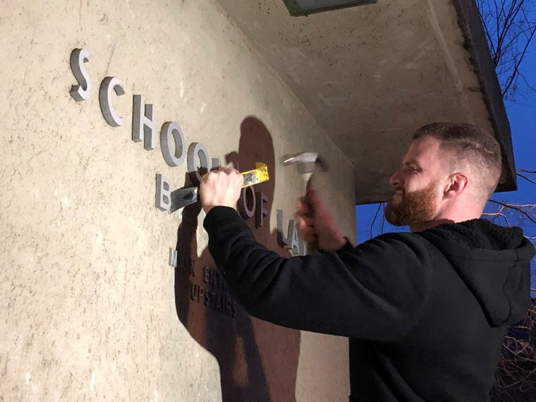 """UC Berkeley carpenter Joe Poppi removes lettering saying """"Boalt Hall"""" from the side of the Berkeley Law building early on Jan. 30, 2020."""