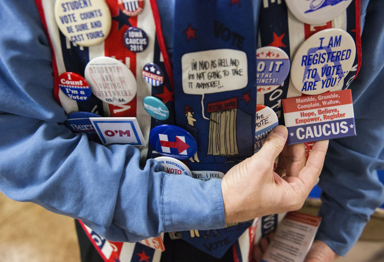 A voter shows off various caucus pins on his vest in Des Moines, Iowa