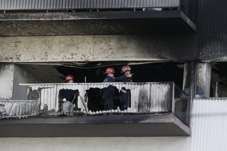 In this Wednesday, Jan. 29, 2020 photo, Los Angeles Fire Department investigators view the charred sixth floor of a residential building in Los Angeles.