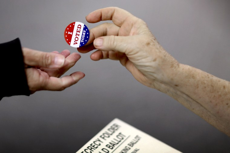 """Image: A voter receives an """"I Voted"""" sticker after casting their ballot in Red Oak, Iowa, in 2014."""
