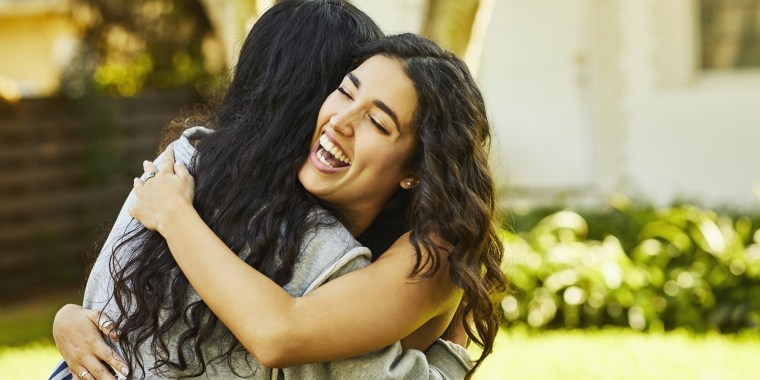 Happy young woman embracing friend at yard