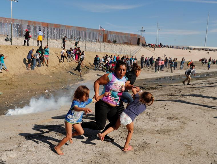 A migrant family runs away from tear gas near the border wall in Tijuana, Mexico, on Nov. 25, 2018.