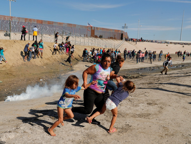 A migrant family runs away from tear gas near the border wall in Tijuana, Mexico, on Nov. 25, 2018.