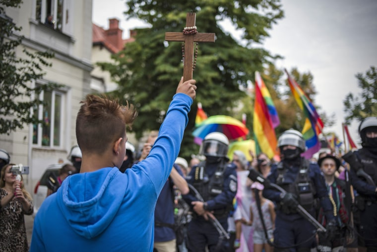 A protester holding a crucifix tries to block the route of an LGBTQ march on Aug. 10, 2019, in Plock, Poland.