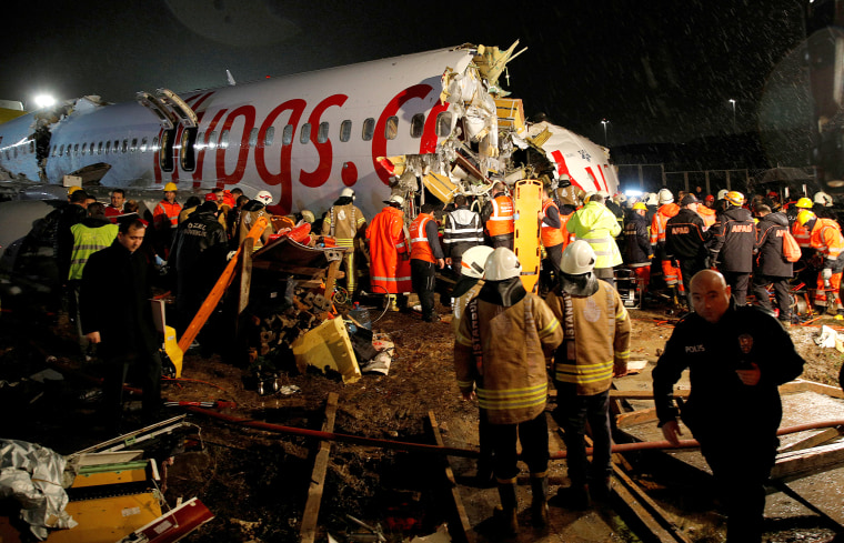 Image: First responders look inside the Pegasus Airlines Boeing 737-86J plane, after it overran the runway during landing and crashed, at Istanbul's Sabiha Gokcen airport